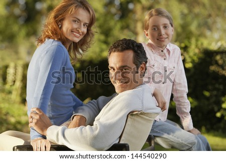 Portrait of happy parents with daughter in backyard - stock photo