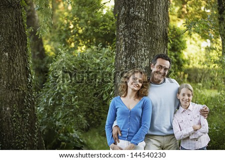 Portrait of happy parents with daughter in park - stock photo