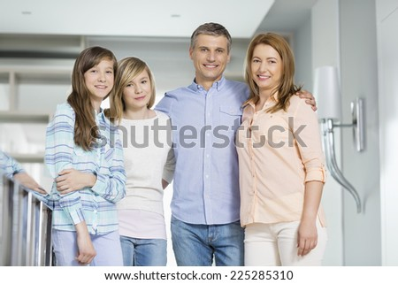 Portrait of happy parents with daughters standing together at home - stock photo