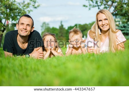 Portrait of happy parents with kids lying at the park