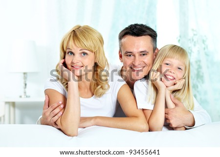 Portrait of happy parents with their daughter spending time at home - stock photo