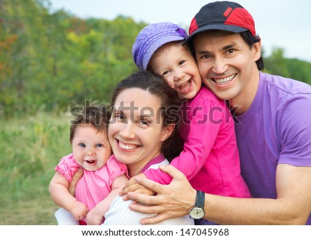 portrait of happy parents  with their little daughters  outdoors