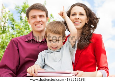 Portrait of happy parents with their son sitting on the bench  with digital tablet  - stock photo