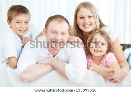 Portrait of happy parents with two children looking at camera at home - stock photo