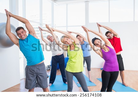 Portrait of happy people doing stretching exercise in yoga class - stock photo