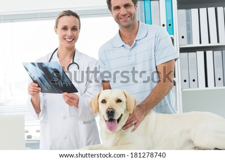 Portrait of happy pet owner and veterinarian with Xray of dog in hospital - stock photo