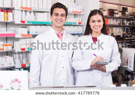 Portrait of happy pharmacist and pharmacy technician in drugstore