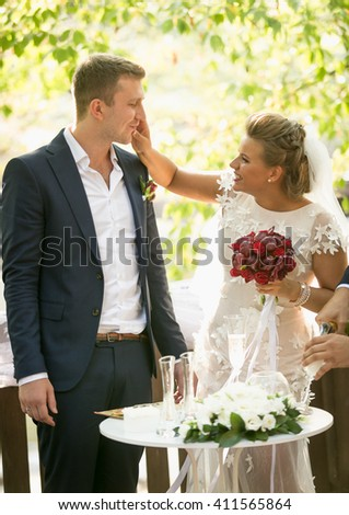 Portrait of happy playful bride and groom at wedding ceremony - stock photo