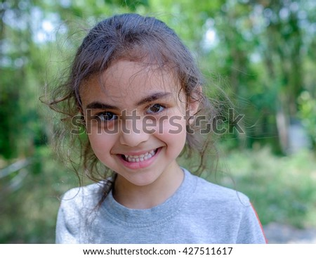 portrait of happy, positive, smiling, playful mixed race asian caucasian girl in park at home