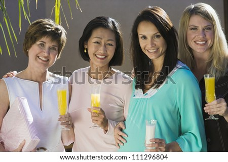 Portrait of happy pregnant woman with friends holding drinks - stock photo