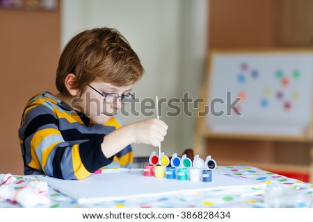 Portrait of happy preschool kid boy with glasses at home making homework. Little child drawing with colorful watercolors and gouache, indoors. School, education concept