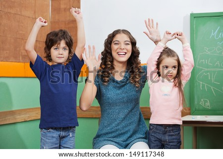 Portrait of happy preschool teacher playing with children in class - stock photo