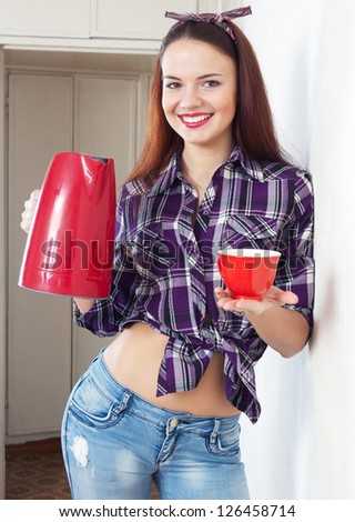 Portrait of happy pretty housewife with red kettle and cup at home interior - stock photo