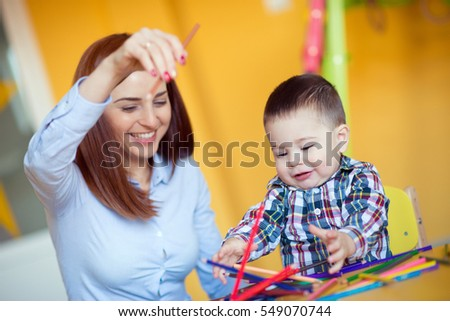 Portrait of happy pretty mother with her toddler son drawing with pencils