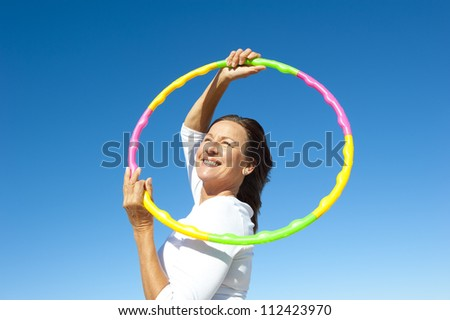 Portrait of happy pretty senior woman exercising with colorful hula hoop, isolated with blue sky as background and copy space.