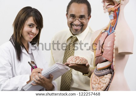 Portrait of happy professor holding organ with student writing notes - stock photo