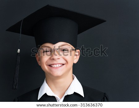 Portrait of happy pupil in mortar board and eyeglasses smiling at camera in classroom - stock photo