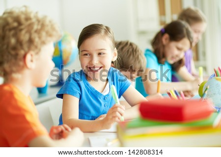 Portrait of happy pupil looking at her classmate at lesson - stock photo
