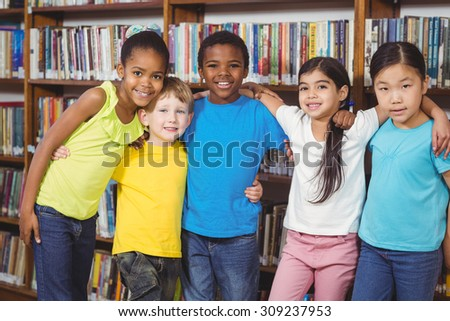 Portrait of happy pupils having arms around in the library in school