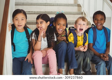 Portrait of happy pupils laughing and sitting on stairs in school - stock photo