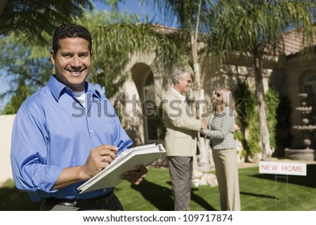 Portrait of happy real state agent holding file folder with couple in background - stock photo