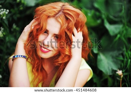 Portrait of happy red-haired woman in Park on a background of green foliage. Girl straightens her hair and laughing merrily, on the right hand stylish bracelet. - stock photo