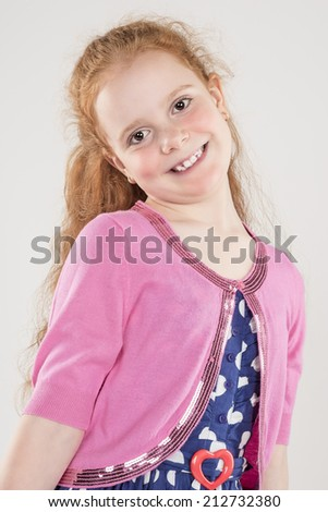Portrait of Happy Redhaired Caucasian Girl wearing Polka dotted Dress. Against White Background. Vertical Image - stock photo