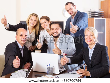 Portrait of  happy relaxed employees sitting at desk