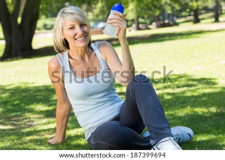 Portrait of happy relaxed woman holding water bottle in the park - stock photo