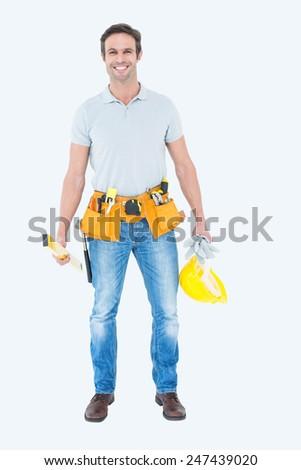 Portrait of happy repairman holding spirit level and hardhat over white background - stock photo