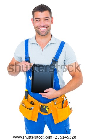 Portrait of happy repairman in overalls holding digital tablet on white background - stock photo