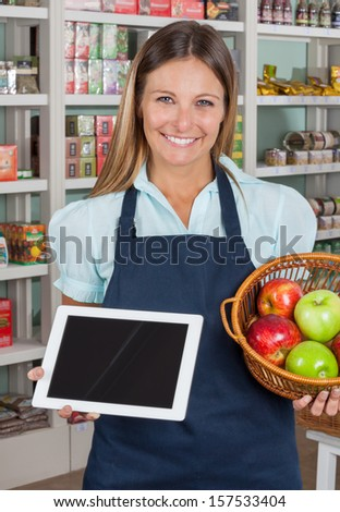 Portrait of happy saleswoman holding digital tablet and fruits basket in grocery store - stock photo