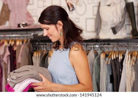 Portrait of happy Saleswoman holding stack of clothes in boutique