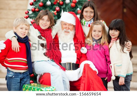 Portrait of happy Santa Claus and children outside house - stock photo