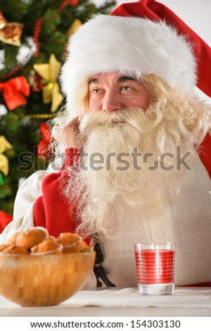 Portrait of happy Santa Claus at home dreaming about something while eating cookies and drinking tea