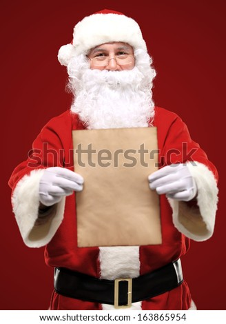 Portrait of happy Santa Claus holding Christmas letter and looking at camera  - stock photo