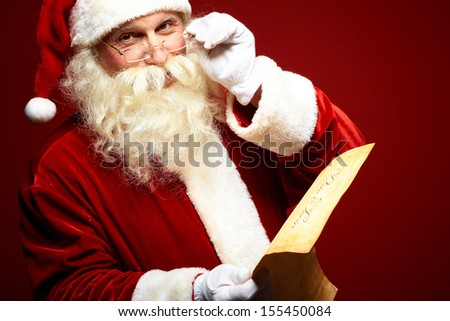 Portrait of happy Santa Claus holding Christmas letter in his hands and looking at camera - stock photo