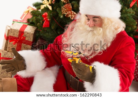 Portrait of happy Santa Claus holding gift helicopter toy in his hands sitting near Christmas tree