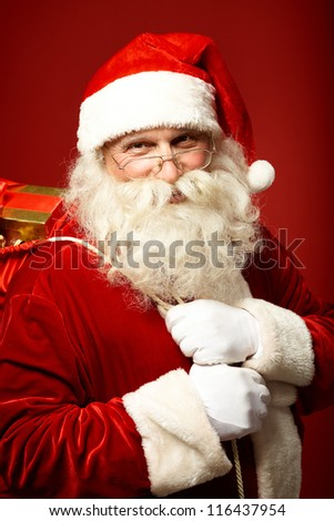 Portrait of happy Santa Claus holding sack with gifts and looking at camera - stock photo