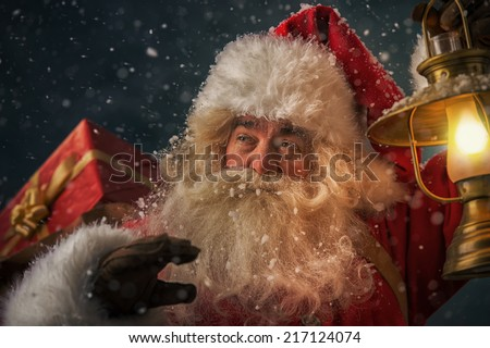 Portrait of happy Santa Claus holding sack with gifts and walking under snowfall with vintage lantern outdoors