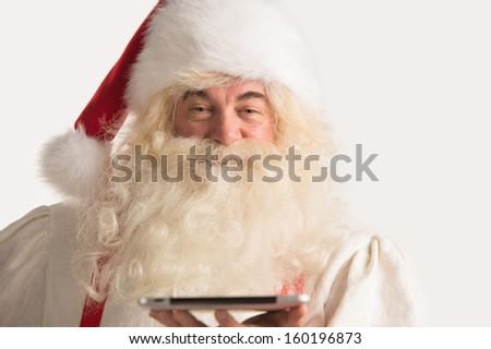 Portrait of happy Santa Claus holding tablet computer in his hands and looking at camera