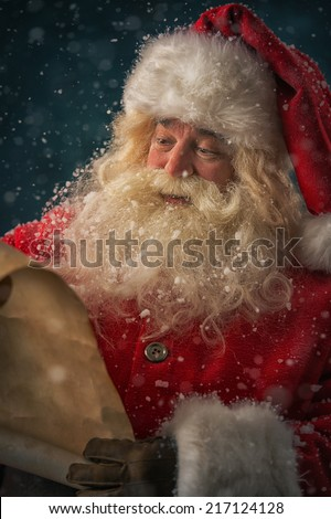 Portrait of happy Santa Claus reading Christmas letter outdoors at north pole under snowfall - stock photo