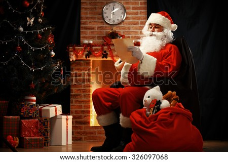 Portrait of happy Santa Claus sitting at his room at home near Christmas tree and big sack and reading Christmas letter or wish list