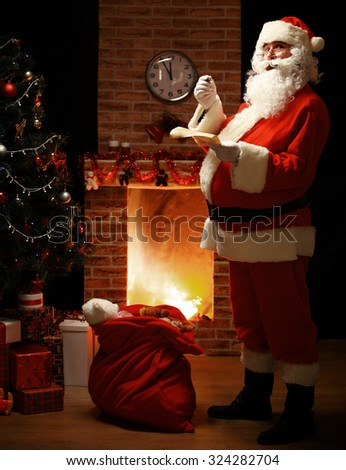 Portrait of happy Santa Claus standing at his room at home near Christmas tree and big sack and reading Christmas letter or wish list - stock photo