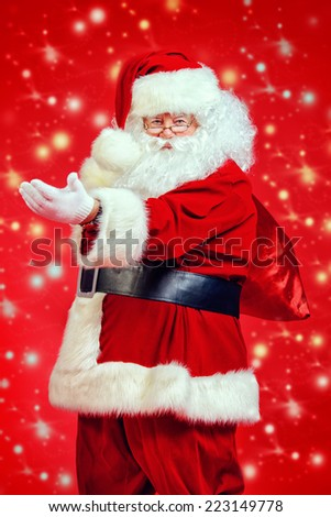 Portrait of happy Santa Claus with a big bag of gifts over festive red background.  - stock photo