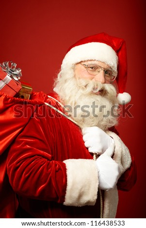 Portrait of happy Santa Claus with big red sack showing thumb up and looking at camera