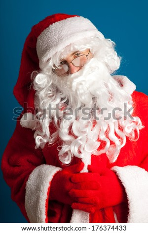 Portrait of happy Santa Claus with glasses look at on camera on blue background.