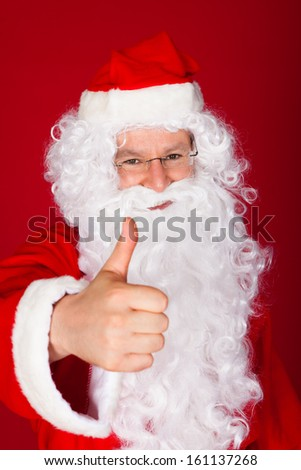 Portrait of happy santa gesturing thumb-up on red background