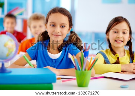 Portrait of happy school children drawing with crayons