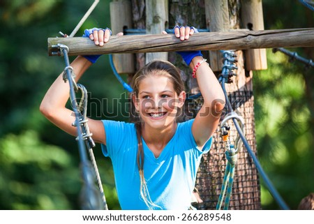 Portrait of happy school girl enjoying activity in a climbing adventure park on a summer day - stock photo